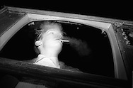 Teenager smoking inside television screen frame.