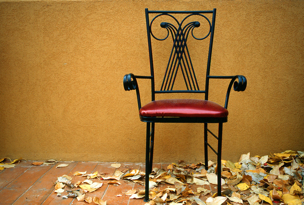 Red chair contrasts with yellow plaster wall, yellow leaves