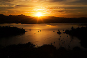 golden sunrise over mangonui harbour with boats and landscape in silhouette, doubtless bay, northland, new zealand