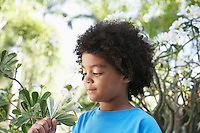 Boy (5-6 years) smelling flowers in garden