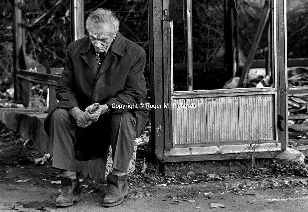 An old man sits at a destroyed bus stop in a city where  buses no longer run, Sarajevo, Bosnia-Herzegovina, February 1993. PHOTO BY ROGER RICHARDS