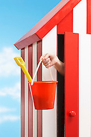 Person holding bucket and spade standing in beach cabin