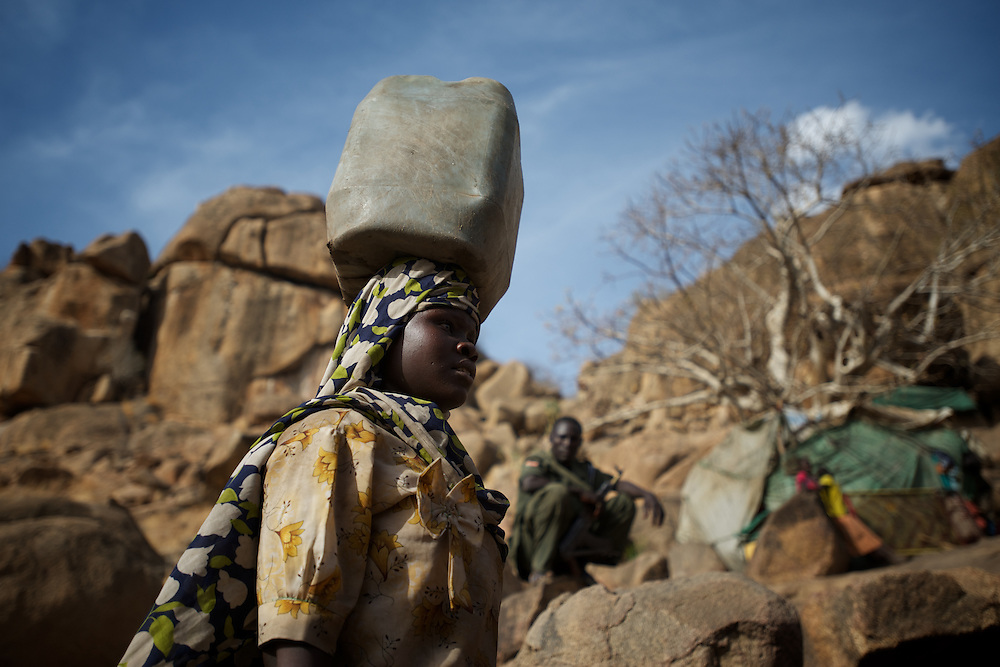 April 28, 2012 - Buram, Nuba Mountains, South Kordofan, Sudan: A Nuba woman walks by carrying water near some caves outside Buram village in South Kordofan's Nuba Mountains...Since the 6th of June 2011, the Sudan's Army Forces (SAF) initiated, under direct orders from President Bashir, an attack campaign against civil areas throughout the South Kordofan's province. Hundreds have been killed and many more injured...Local residents, of Nuba origin, have since lived in fear and the majority moved from their homes to caves in the nearby mountains. Others chose to find refuge in South Sudan, driven by the lack of food cause by the agriculture production halt due to the constant bombardments of rural areas. (Paulo Nunes dos Santos/Polaris)