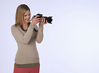 Young (20-25 years) female photographer holding camera studio shot