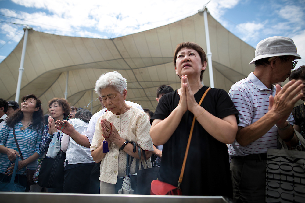 NAGASAKI, JAPAN - AUGUST 9 : Visitors pray for the atomic bomb victims in front of the Peace Statue during the 71st Anniversary of atomic bombing on Nagasaki at Nagasaki Peace Park, Nagasaki, southern Japan, Tuesday, August 9, 2016. Japan marked the 71st anniversary of the atomic bombing on Nagasaki. On August 9, 1945, during World War II, the United States dropped the second Atomic bomb on Nagasaki city, killing an estimated 40,000 people which ended World War II. (Photo by Richard Atrero de Guzman/NURPhoto)