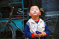 """China, Beijing, 2008. A boy shows no fear of strangers as he watches the goings- on in his """"hutong,"""" or traditional neighborhood. Many of China's children will grow up in a very different world their parents experienced.."""
