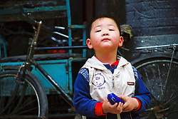 "China, Beijing, 2008. A boy shows no fear of strangers as he watches the goings- on in his ""hutong,"" or traditional neighborhood. Many of China's children will grow up in a very different world their parents experienced.."