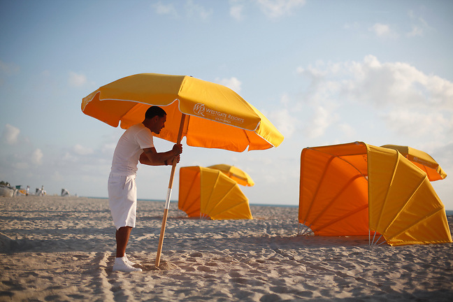 4/3/13---Miami Beach, Florida---Photo by Angel Valentin<br /> Julio Pagan, a beach attendant for Westgate Resorts, sets up beach umbrellas, cabanas and chairs on the sands of Miami Beach near 36 street in the early hours of the morning.