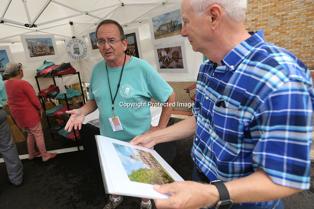 Kim Hunt, a photographer from Brandon, talks with David Lesley, of Tupelo, about his photography as Lesley holds photos he has picked out to buy after visiting Hunt's booth at the GumTree Arts Festival Saturday morning in Tupelo.