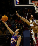 MORNING JOURNAL/DAVID RICHARD.Steve Nash, left, of Phoenix makes a reverse layup while defended by Cleveland's Drew Gooden .