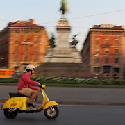 Fast moving yellow Vespa scooter in traffic circle with Garibaldi monument, Milan, Italy