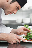 Male chef preparing salad in kitchen close-up