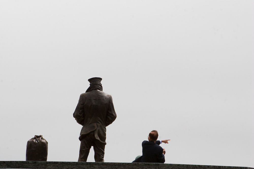 Asian tourist interacting with the Lone Sailor's Memorial in Golden Gate Park, San Francisco California.