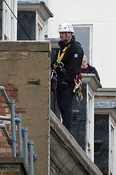 © London News Pictures. 11/06/2013. London, UK. A police officer in harness on the roof of the building. Police waiting to raid a squat at abandoned police station on Beak Street, London which is being used by Anti-G8 activists as their headquarters ahead of a demonstration in central London today (Tues) The G8 Summit is due to take place in Norther Ireland early next week.  Photo credit: Ben Cawthra/LNP