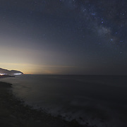The lights of cars outline highway 1 along the Southern California shoreline as the milky way can be made out in the sky. As seen from Point Mugu.