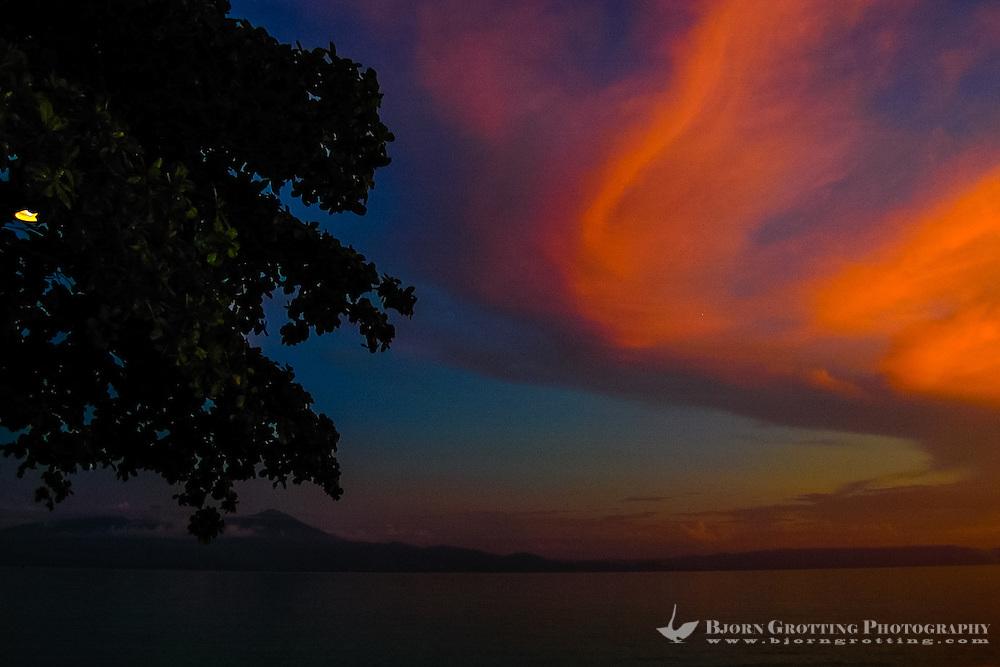 Indonesia, Sulawesi, Bunaken. Sunset at Bunaken. Looking towards Manado city.
