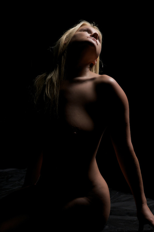 Sensual caucasican blonde seated nude in dim light.