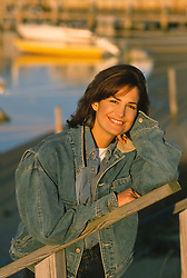 portrait of a woman leaning against a bannister at a boat dock