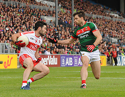 Mayo&rsquo;s Ger Cafferkey tries to contain Derry&rsquo;s Danny Heavron.<br /> Pic Conor McKeown