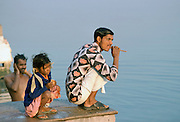 Indian man cleaning his teeth using traditional method while crouching by the river, India