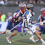 Ryan Young #27 of the Charlotte Hounds keeps the ball from Mitch Belisle #85 of the Boston Cannons during the game at Harvard Stadium on May 17, 2014 in Boston, Massachuttes. (Photo by Elan Kawesch)