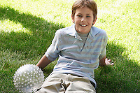Smiling Boy Sitting in the Grass