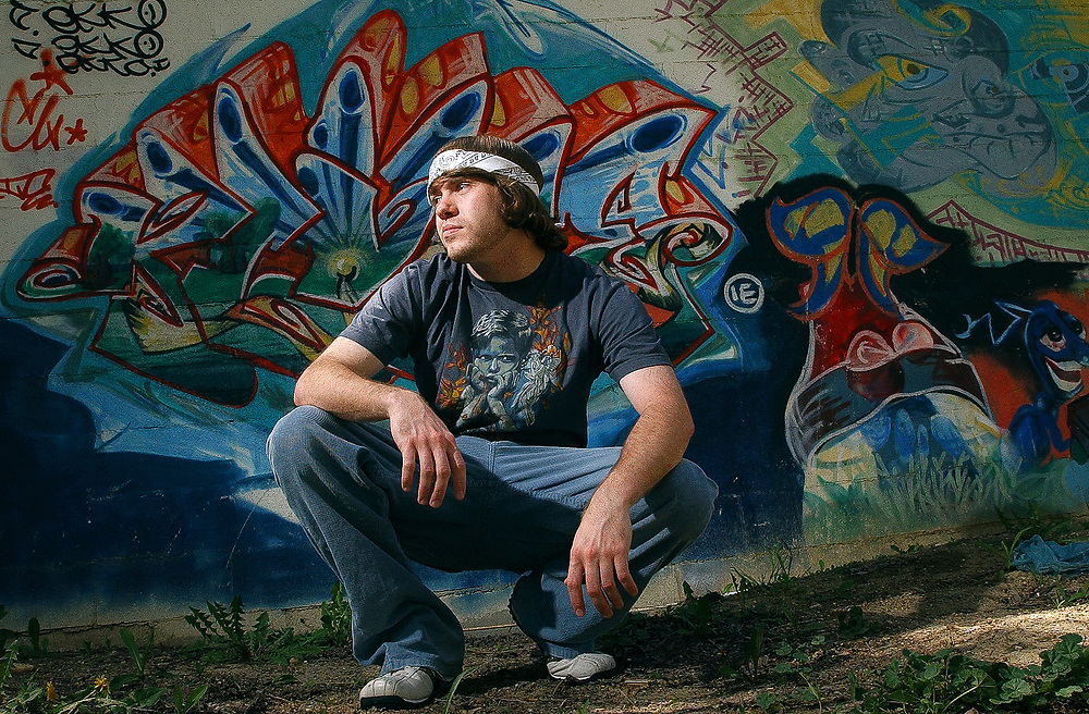 Andy Mason, graffiti artist, poses at one of his first &quot;legal&quot; works along 3rd Ave in Longmont, April 28, 2007.  He painted the white cinder block garage wall several years ago with the permission of the homeowner.<br /> <br /> (Daily Times-Call, Bradley Wakoff)