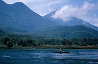 A man paddles a traditional cayuco (canoe) across Lake Atitlan, Guatemala
