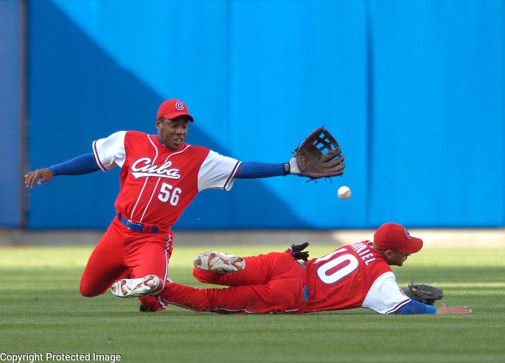 Team Cuba's #56 Carlos Tabares and #10 Yulieski Gourriel cant come up with the ball off the at of Team Dominican Republic's Moises Alou in the 9th inning in Semi-Final action of the World Baseball Classic at PETCO Park, San Diego, CA.