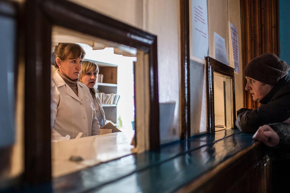 ZIMOGORYE, UKRAINE - MARCH 15, 2015: Patients retrieve their files from an office at Zimogoryivskaya Ambulatory in Zimogorye, Ukraine. CREDIT: Brendan Hoffman for The New York Times