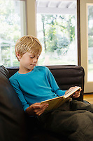 Young boy (5-6) sitting on sofa reading book