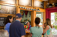 Liz Breton serves customers in the newly opened indoors seating space at Ben & Jerry's in Meredith's Mill Falls Marketplace during their grand opening celebration on Saturday afternoon.  (Karen Bobotas/for the Laconia Daily Sun)