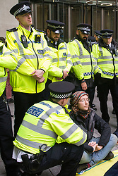 London, UK. 11 October, 2019. A police officer issues a warning under Section 14 of the Public Order Act 1986 to a climate activist from Extinction Rebellion blocking the main entrance to the BBC's New Broadcasting House on the fifth day of International Rebellion protests. The activists were demanding that the broadcaster 'tell the truth' regarding the climate emergency.