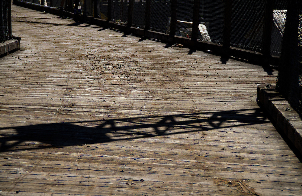 The crane's shadow is reflected on the wooden deck on the Elwha Dam