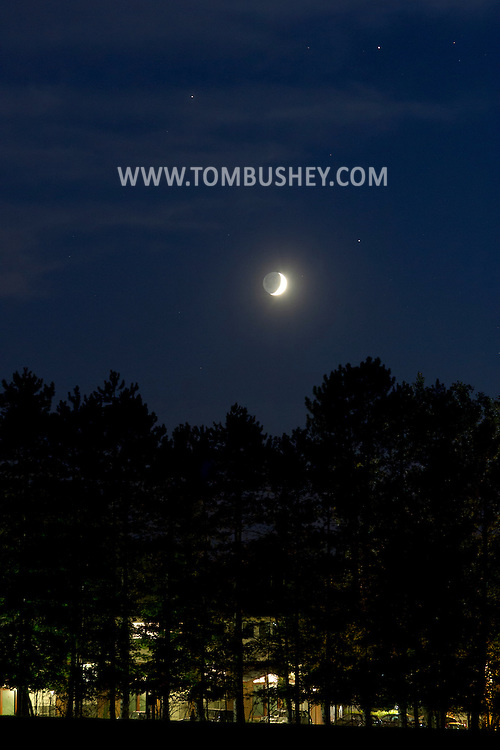 Middletown, New York - The crescent moon is joined in the western sky by the planets Mars, upper left, Saturn, upper right, and the bright star Spica, lower right after sunset on  Aug. 21, 2012.
