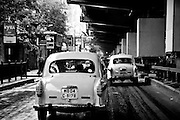 Bright yellow taxis driving down the streets of Kolkata (Calcutta), India in the rain. Black and white.