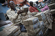 Money changers sit behind stacks of Somaliland Shilling notes in Hargeisa, Somaliland.