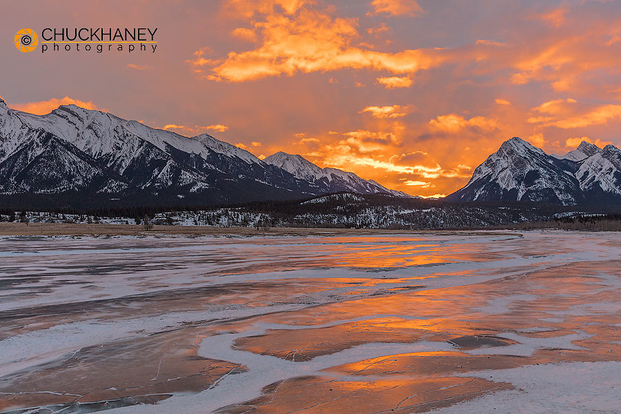 Brilliant sunrise reflects on winter ice of Abraham Lake near Nordegg, Alberta, Canada