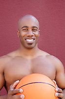 Portrait of a shirtless African American man with basketball over colored background