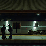 Workers are seen on the Amtrak platform beside the Pacific Surfliner at Union Station in Los Angeles.