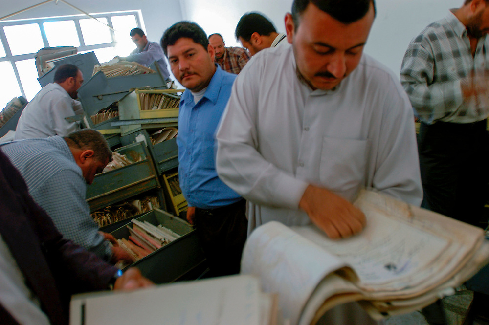 Volunteers at the Committee of Free Prisoners search through documents recovered from the regime's secret service in search of information about missing family members. The committee recovers and organizes the archives to aid Iraqis to find thousands of missing people.<br /> Baghdad, Iraq. 28/04/2003.
