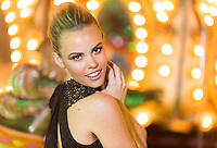 Beautiful young woman in a venue with party lights dressed in a stylish sexy black dress looking back over her shoulder at the camera with a smile