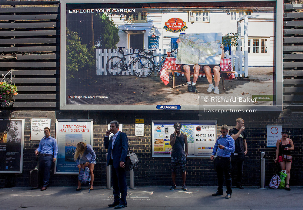 London commuters stand outside London's Paddington mainline Station to smoke or make calls beneath a large billboard about the countryside ad for brewer Shepherd Neame. Urban people are seen below the idyllic scene of rural England, tourists enjoying the peaceful great outdoors with the help of a map and bikes while below are the exact opposite: City dwellers trying to de-stress or keep in touch with the world.