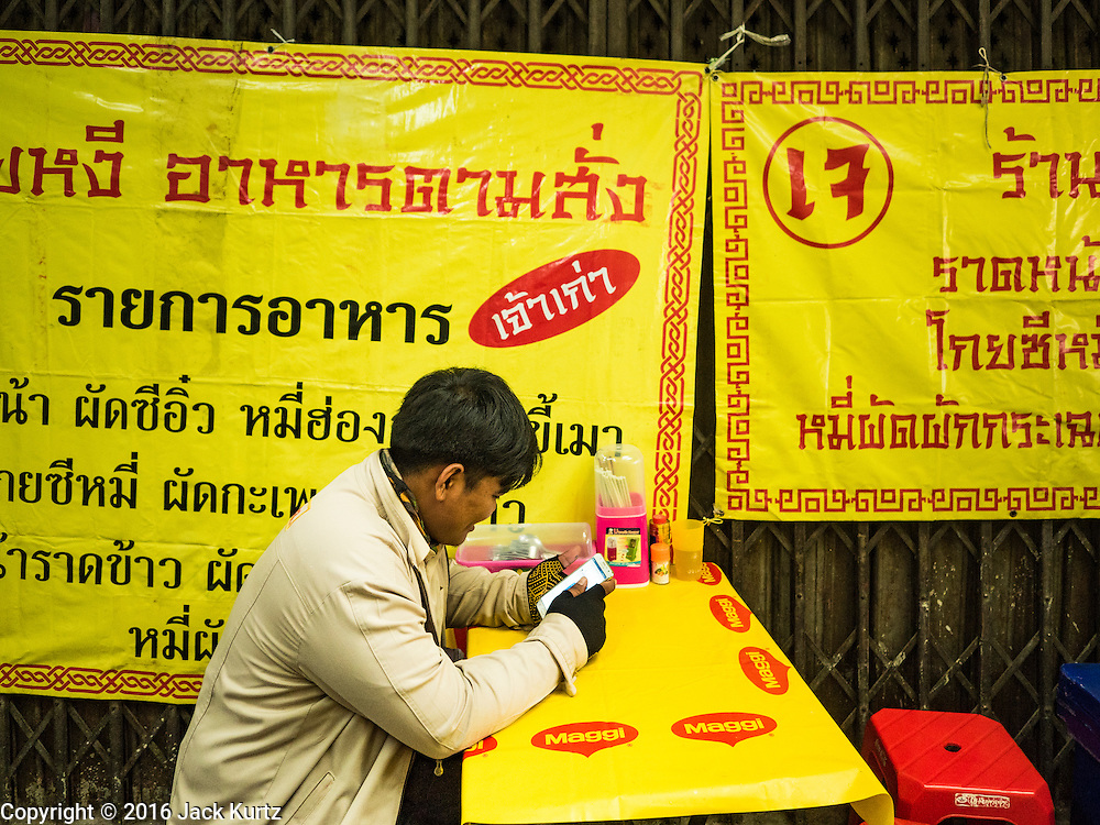 04 OCTOBER 2016 - BANGKOK, THAILAND: A man waits for his vegetarian dinner during the Vegetarian Festival at the Chit Sia Ma Chinese shrine in Bangkok. The Vegetarian Festival is celebrated throughout Thailand. It is the Thai version of the The Nine Emperor Gods Festival, a nine-day Taoist celebration beginning on the eve of 9th lunar month of the Chinese calendar. During a period of nine days, those who are participating in the festival dress all in white and abstain from eating meat, poultry, seafood, and dairy products. Vendors and proprietors of restaurants indicate that vegetarian food is for sale by putting a yellow flag out with Thai characters for meatless written on it in red.     PHOTO BY JACK KURTZ