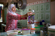 Iin Hartini pouring chillies in to the blender in her kitchen.<br /> <br /> In 2007 Iin started her own business selling Nasi Goreng (fried rice). <br /> <br /> She makes it in bulk for the school canteen to sell to children who have their breakfast at school. <br /> <br /> Prior to signing up to Usaha Wanita Iin had been beginning to feel demotivated about her work and for a short time ceased making the rice. Since receiving the advice and mentoring she has become reenergised for her business and her profits have tripled.