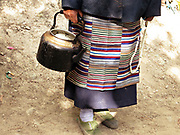A Tibetan woman holds a kettle and prayer beads, the belongings she chose to carry on the Kawagarbo kora, the two-week-long circumambulation of Kawagarbo in Tibet and Yunnan, China; September, 2013.