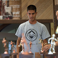 080214      Cayla Nimmo<br /> <br /> Andy Yazzie and Autumn Newell look at all the trophies the cross country team has ever won at Rehoboth High School on Saturday during a reunion. Yazzie ran for the school from '96-'99 and Newell from '93-'97. She will take over as head coach for the team beginning this school year.