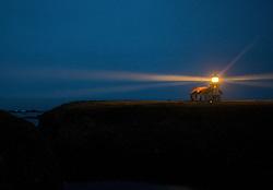 The Point Cabrillo lighthouse stands as a beacon at dusk along Mendocino cliffs near Mendocino, California, USA.