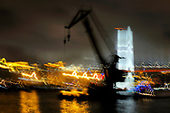 Shanghai city centre, China. Semi abstract. Barge crane on the Huangpu River in front of the Nan Pu Bridge at night
