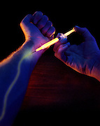 An artery turns yellow as a man gives himself a shot in the arm with a glowing syringe.Black light